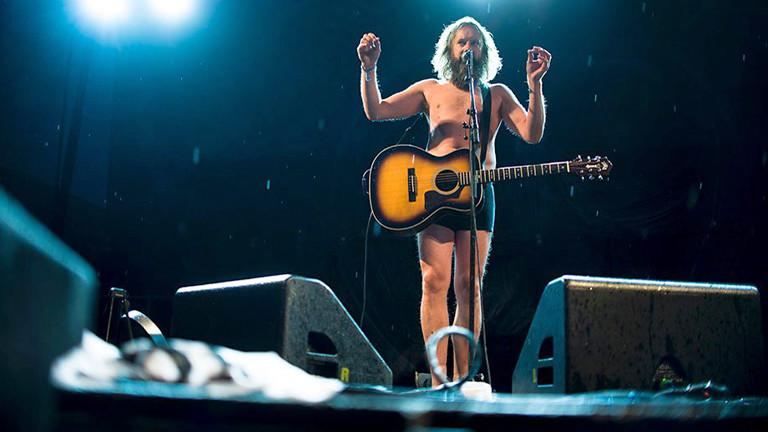 Ein Mann in Unterhose steht auf der Bühne. Er hat lange Haare und Bart und eine Gitarre umhängen.