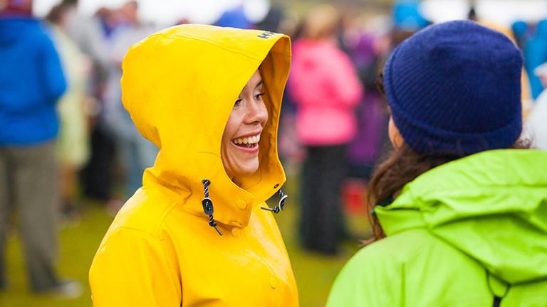 Eine Frau mit gelber Regenjacke mit Mütze unterhält sich mit einer Frau in grüner Regenjacke. Sie lacht.