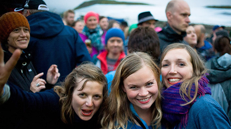 Drei Frauen lachen in die Kamera, sie sind umgeben von Menschen.