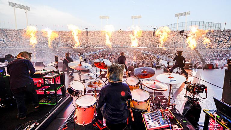 Aufnahme einer Band auf der Bühne von hinten, die Musiker, die alle Wolfsmasken tragen, blicken Richtung Stadion, das mit tausenden von Menschen gefüllt ist.