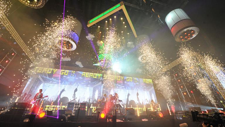 Auf einer Bühne gibt es viel visuelle Effekte und Lichtspiele, eine Band spielt.