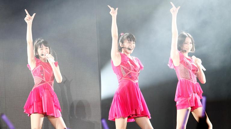 Drei Sängerinnen stehen auf der Bühne nebeneinander. Sie tragen Headset und rosa Kleider.