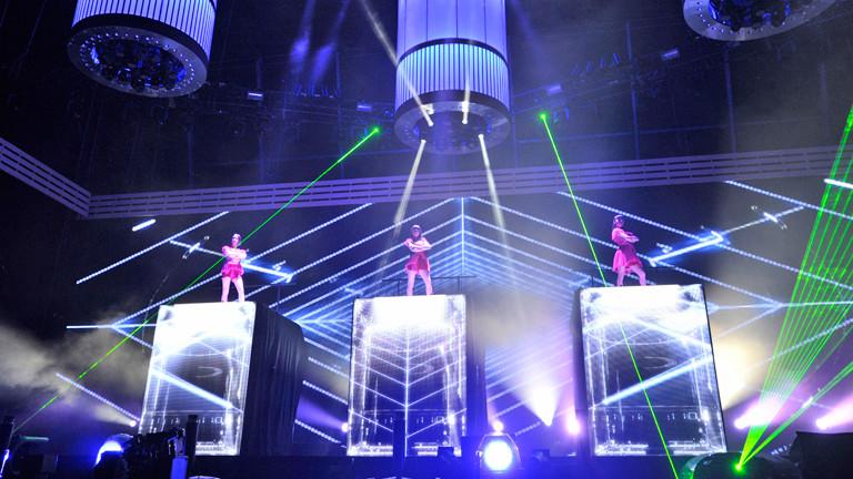 Drei Frauen stehen auf drei durchsichtigen hohen Boxen auf der Bühne.