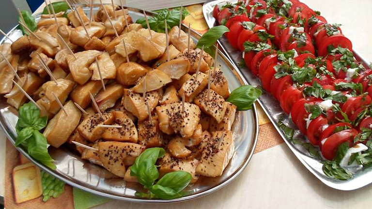 Zwei silberne Platten: Auf der einen liegen Fischstücke, auf der anderen Tomaten mit Mozzarella.