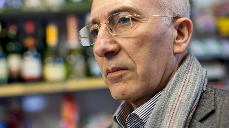 Mitat Özdemir leicht im Profil, er trägt eine Brille und Schal über Hemd und Jacket; Bild: dpa