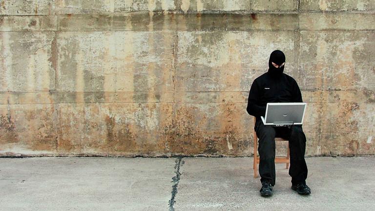 Symbolbild eines Hackers der vermummt mit LapTop auf einem Stuhl sitzt.