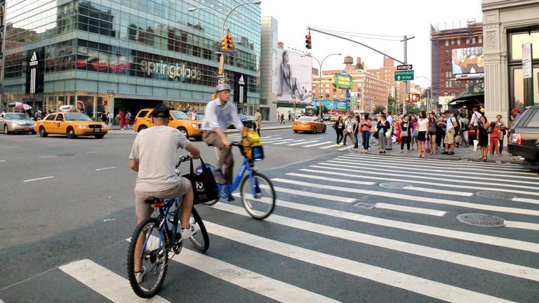 Fahrradfahrer überqueren auf einem Zebrastreifen die Kreuzung Broadway und Houston Street in Manhattan.
