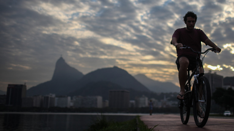 Ein Mann fährt am Strnd von Rio de Janeiro Fahrrad.