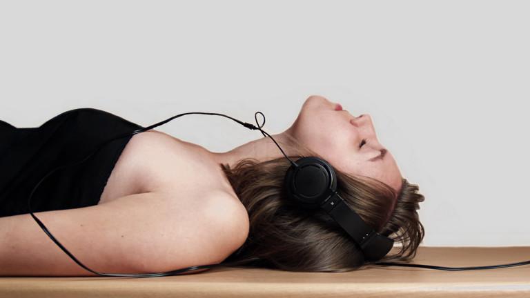 Eine Frau liegt auf dem Rücken. Sie trägt einen Kopfhörer und hat die Augen geschlossen. Ihr Oberkörper ist auf dem Foto zu sehen.