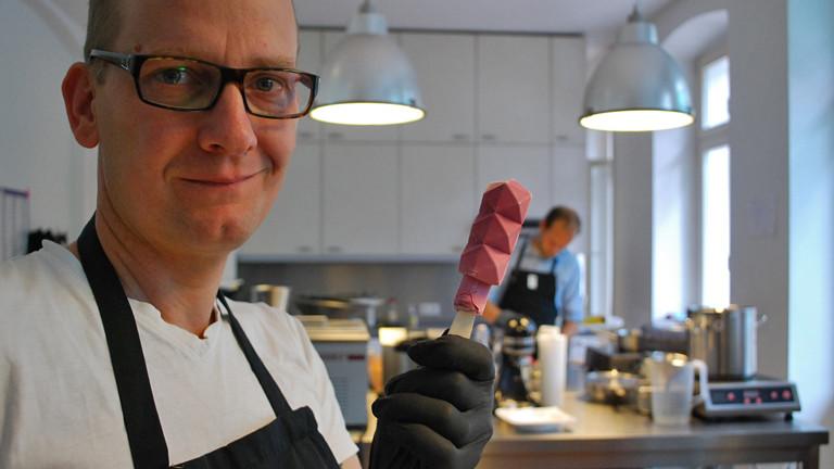 David Marx steht links im Bild. Er trägt eine Brille mit schwarzem Rahmen. In der linke Hand hält er ein Eis am Stiel. Im Hintergrund ist eine Küche zu sehen.