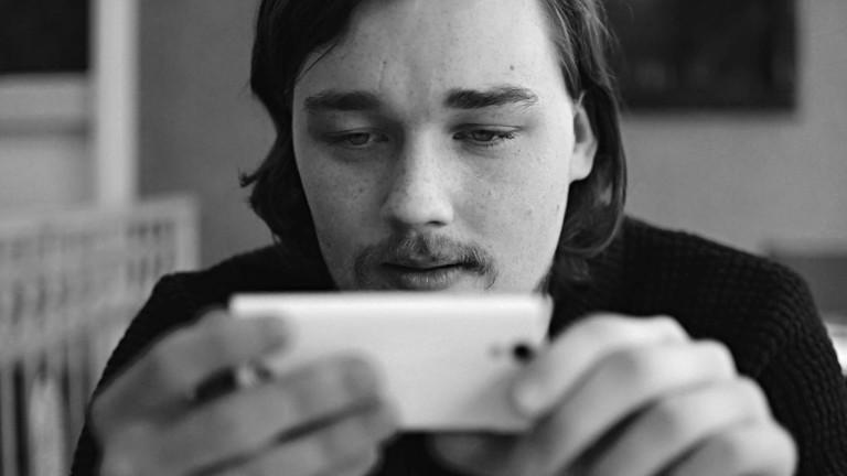 Schwarz-Weiß-Foto. Ein Mann mit Schnauzer schaut auf eine Smartphone, das er mit beiden Händen festhält.