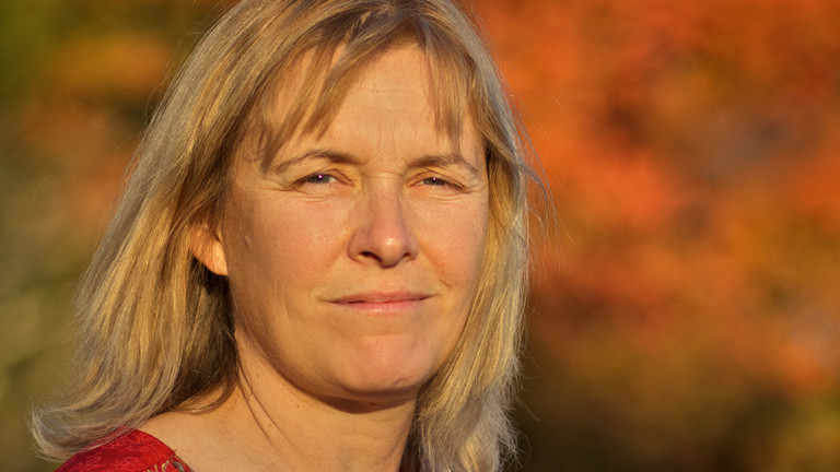 Portrait von Valerie Curtis. Sie hat schulterlange, blonde Haare. Herbstsonne und gefärbte Bäume im Hintergrund.