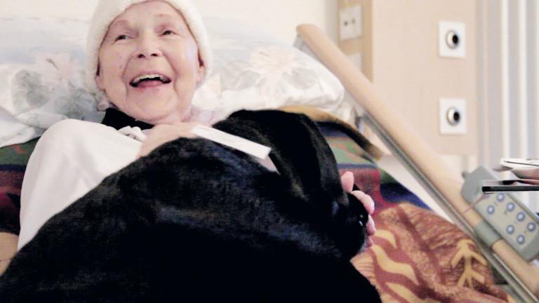"""Ausschnitt aus dem Film """"Zeit zu leben"""". Eine alte Dame liegt in einem Bett und lacht. sie trägt eine Mütze."""