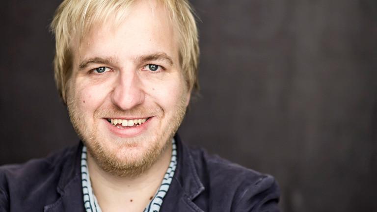 Portrait von David Denk. Er hat blonde kurze Haare und trägt Bart.