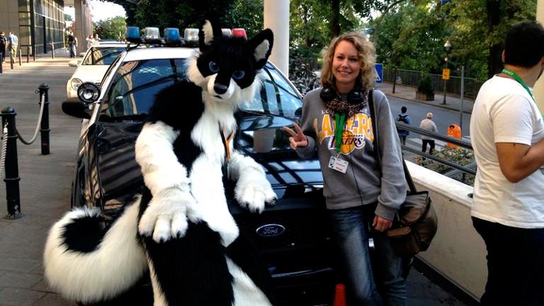 Posing mit einem Husky-Furry-Fan vor einem amerikanischen Polizei-Auto beim Eurofurence in Berlin.