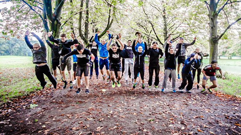 Männer und Frauen in Sportkleidung springen in die Luft und reißen die Arme nach oben. Sie stehen auf einem Waldweg.