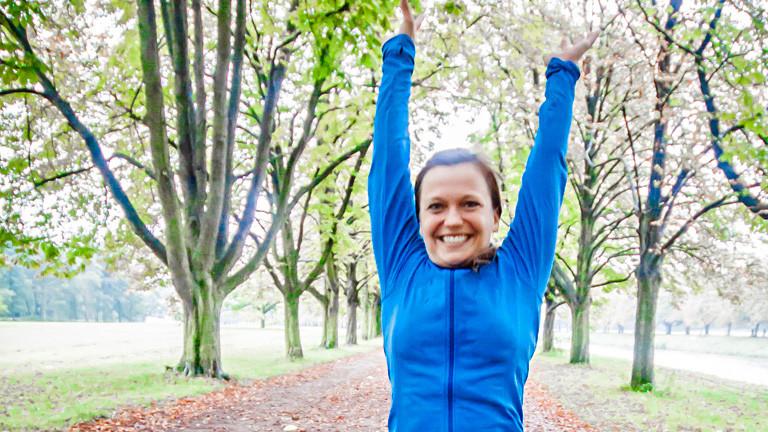 Anita Horn reißt die Arme nach oben und lacht. Sie steht auf einem Waldweg, trägt Sportkleidung.