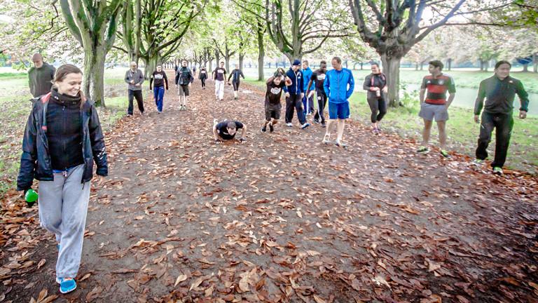 Auf einem Waldweg gehen Männer und Frauen in Sportkleidung entlang. In der Mitte sind zwei Männer: Einer macht eine Liegestütze, der andere einen Strecke-Hochsprung.