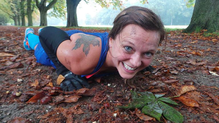 Anita Horn macht eine Liegestütze auf einem Waldweg voll mit Laub. Sie lächelt angestrengt in die Kamera.