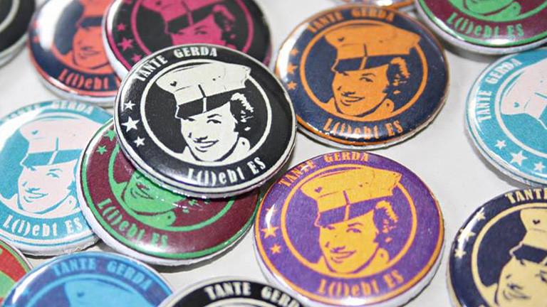 """Bunte Buttons auf denen eine gezeichnete Frau mit Uniformmütze abgebildet ist. Darüber steht """"Tante Gerda"""", darunter """"L(i)ebt ES""""."""