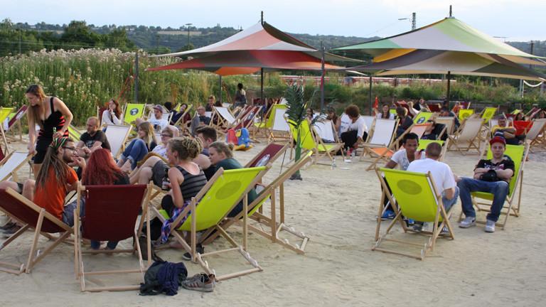 Auf einem Platz mit Sand sitzen viele junge Leute in Strandliegen. Ein paar große Sonnenschirme stehen zwischen den Stühlen.