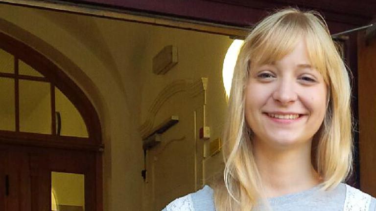 Portrait von Valerie Wolf. Sie steht vor dem Eingangstor der Schule. Hat halblange blonde Haare. Lächelt in die Kamera.
