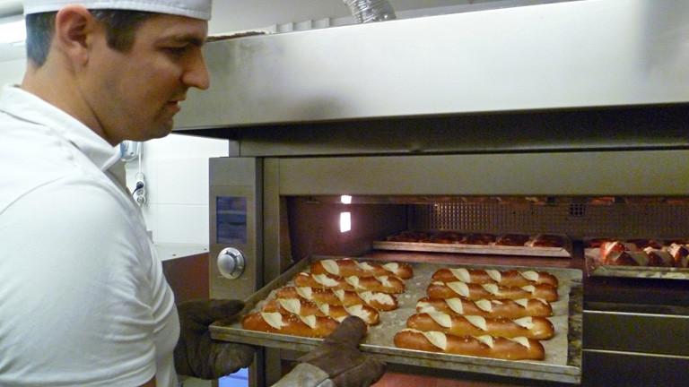 Christian in weißem T-Shirt und mit weißer Haube holt ein Bleck mit fertigen Laugenstangen aus einem Bäcker-Ofen.