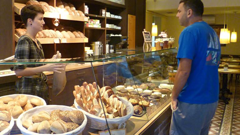 Blick in den Verkaufsraum von Annas Bakery. In der Auslage liegen Brötchen, Laugenwerk. Anna bedient einen Kunden.