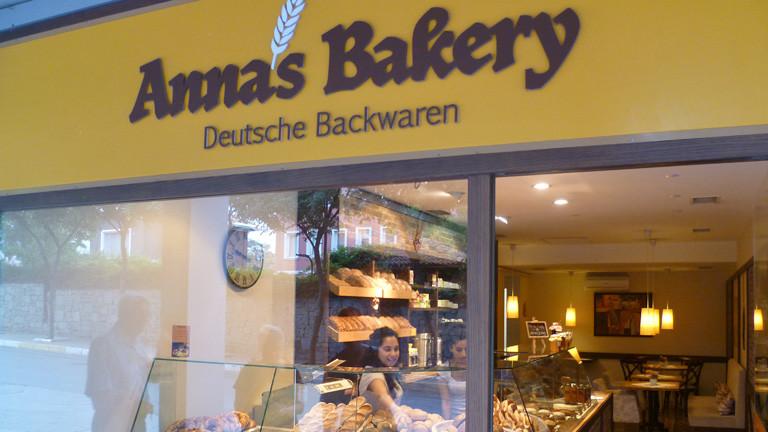 """Blick von außen auf Annas Bäckerei. Über der Ladenfront steht """"Annas Bakery. Deutsche Backwaren""""."""