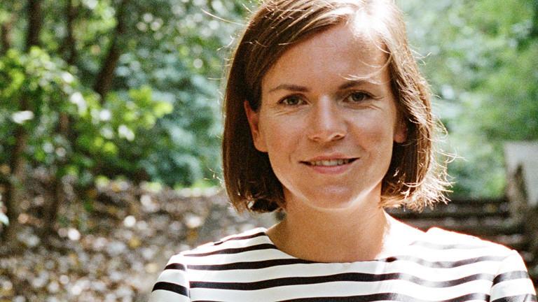 Portrait von Mary Scherpe. Sie steht draußen in der Natur, hinter ihr sind Bäume. Sie hat dunkle Haare und braune Augen. Die Haare sind kinnlang.