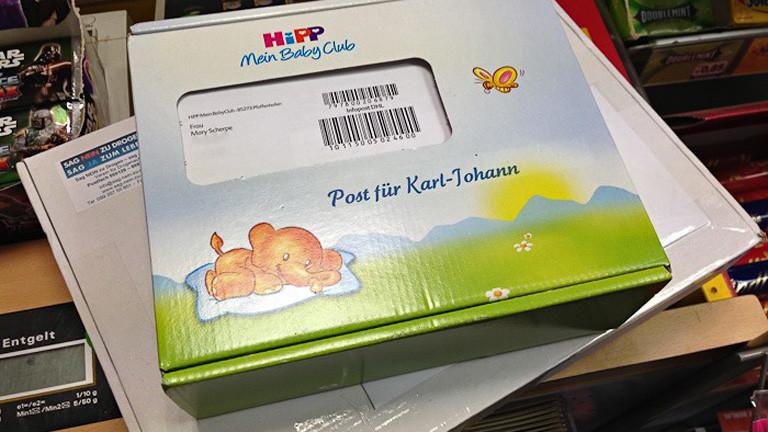 """Ein Paket von Hipp liegt auf einem weiteren Paket, """"Post für Karl-Johann"""" steht darauf."""