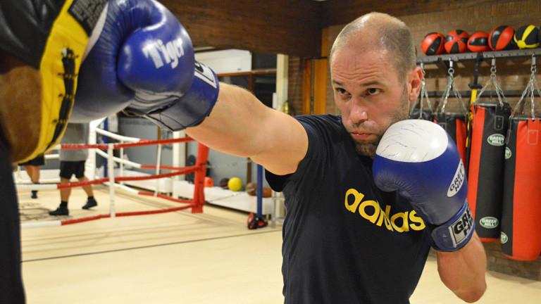 Ein Mann mit Boxhandschuhen schlägt mit seiner Rechten eine Art Sandsack ein.
