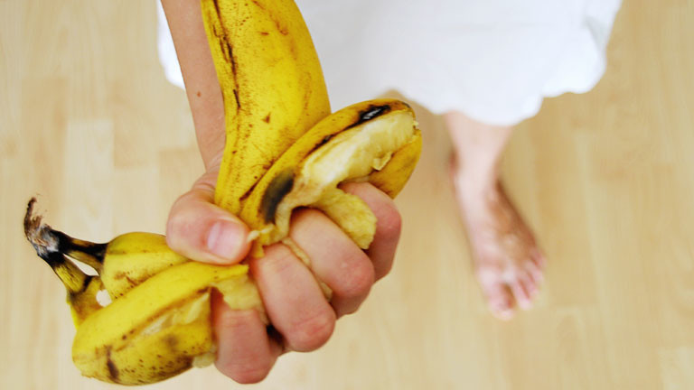Eine Frau zerdrückt eine Bananenschale in der Hand.