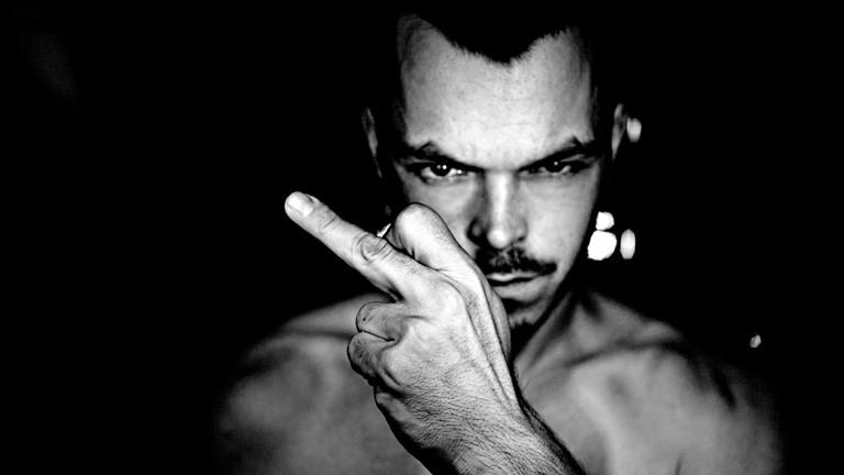 Schwarz-Weiß-Foto. Ein Mann blickt finster in die Kamera, mit nacktem Oberkörper. Er hält seine linke Hand vor sich mit ausgestrecktem Mittelfinger. Der Hintergrund ist schwarz.