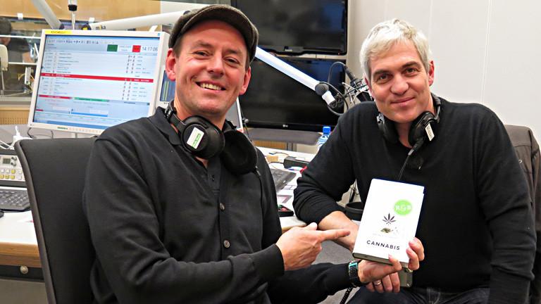 Rainer Schmidt und Moderator Manuel Unger sitzen im Studio. Unger hält das Buch von Schmidt und zeigt darauf.