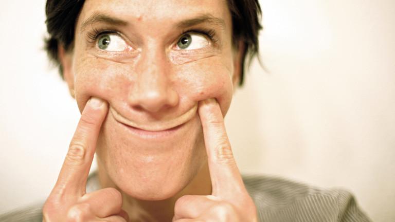 Eine Frau zieht mit ihren beiden Zeigefingern ihre Mundwinkel nach oben. Sie hat grüne Augen und blickt nach rechts.