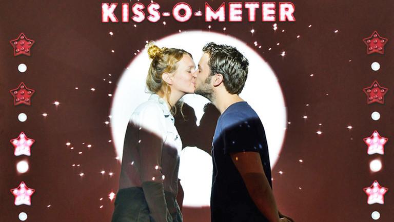 Eine Frau und ein Mann küssen sie sich. Sie stehen im Scheinwerferlicht. Hinter ihnen auf einer Wand funkeln Sterne und in Leuchtbuchstaben steht Kiss-O-Meter.