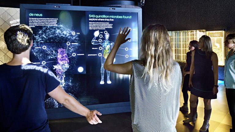 Auf einem körpergroßen Bildschirm ist ein Mensch abgebildet. Davor stehen ein Mann und eine Frau und bewegen ihre Arme. Der Körper auf der Leinwand scheint die Bewegung der Frau abzubilden.