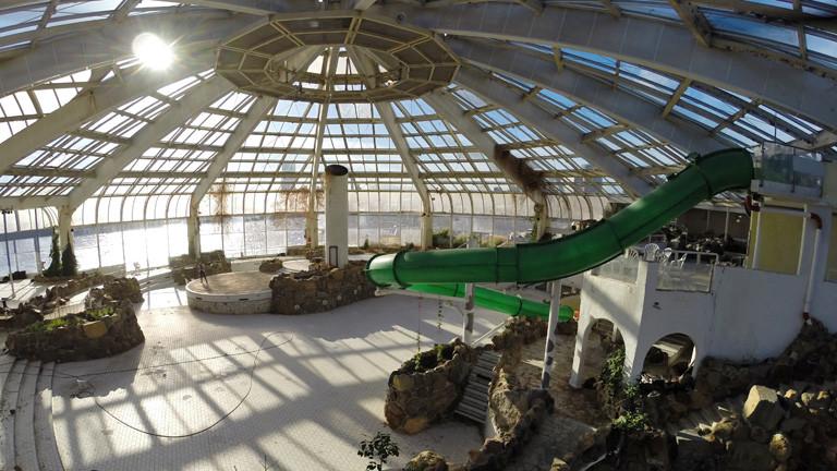 Blick in eine leerstehende Schwimmhalle mit Glaskuppel und verglasten Außenseiten. Unter der Kuppel war einmal das Wellenbad. Rechts ist eine grüne Rutschbahn.