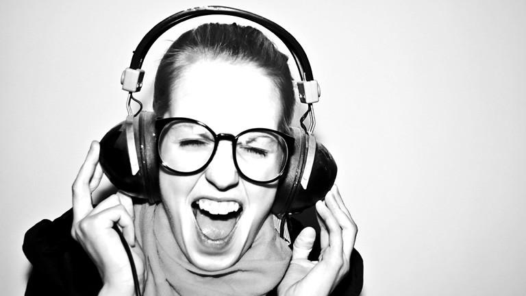 Schwarz-Weiß-Foto. Eine Frau trägt Kopfhörer und Brille. Sie kneift die Augen zusammen und hat den Mund weit geöffnet.