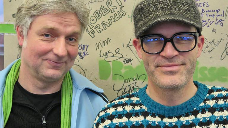 Markus Berges und Ekki Maas stehen vor der DRadio Wissen-Wand mit den Unterschriften der Studiogäste.
