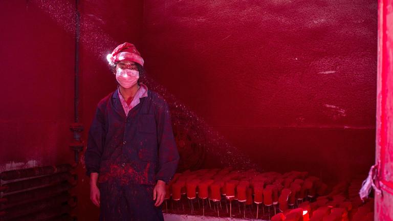 Ein Arbeiter steht mit Weihnachtsmütze bekleidet in einem Raum, der rot von Farbspritzern ist. Hinter ihm stehen aufgereiht zum Trocknen rote Weihnachtsmännerschuhe; Bild: dpa