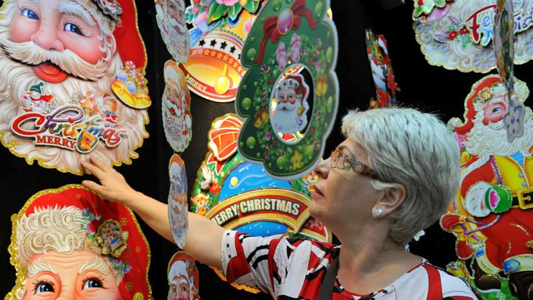 An einer Wand hängt Weihnachtsdekoration. Unter anderem Weihnachtsmänner vermutlich als Aufkleber. Eine Frau steht davor und schaut sich die Deko an; Bild: dpa