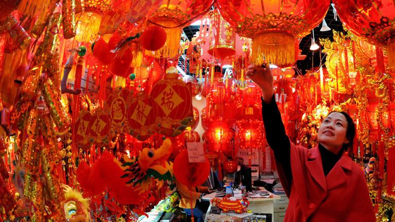 Eine Chinesin steht in einem Raum voller roter Lampions. Alles Deko für das Neujahrsfest in China; Bild: dpa