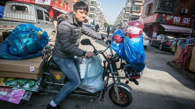 In der chinesischen Stadt Yiwu sitzt ein junger Mann auf einem Moped, das mit Weihnachtsdeko bepackt ist; Bild: dpa