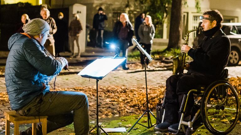 Ein Geiger und ein Saxophonist musizieren auf einem Grünstreifen.