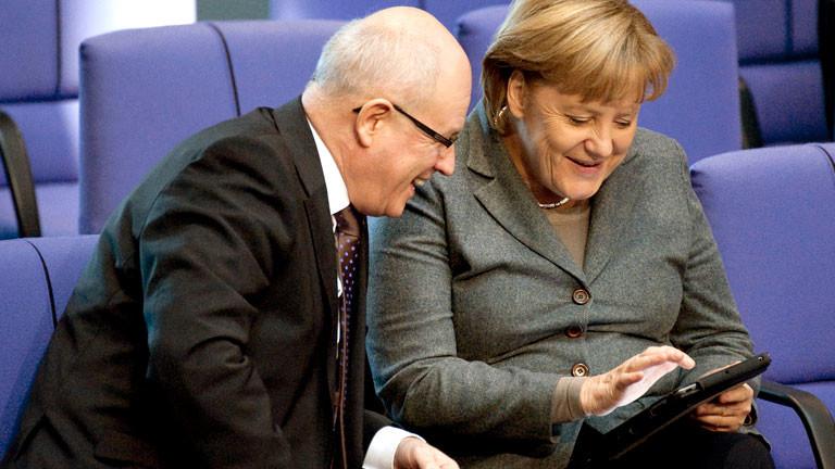 Der Unions-Fraktionsvorsitzende Volker Kauder und Bundeskanzlerin Angela Merkel (CDU) beschäftigen sich im Bundestag in Berlin mit einem iPad.