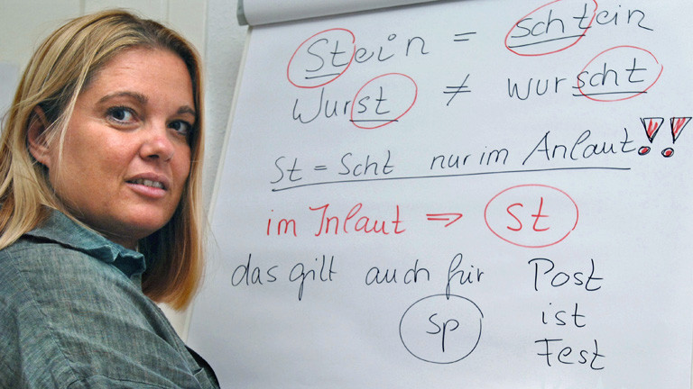 Die Sprecherzieherin Ariane Willikonsky zeigt auf einer Tafel den Unterschied zwischen schwäbischem Dialekt und Hochdeutsch; Bild: dpa