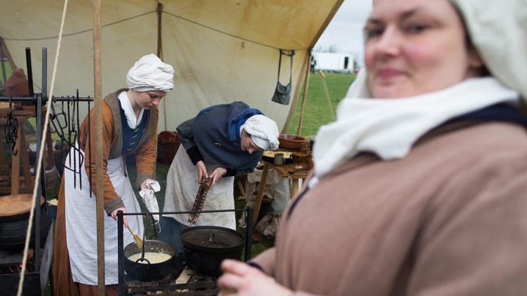 Frauen, die sich als mittelalterliche Mägde und Bäuerinnen verkleidet haben.