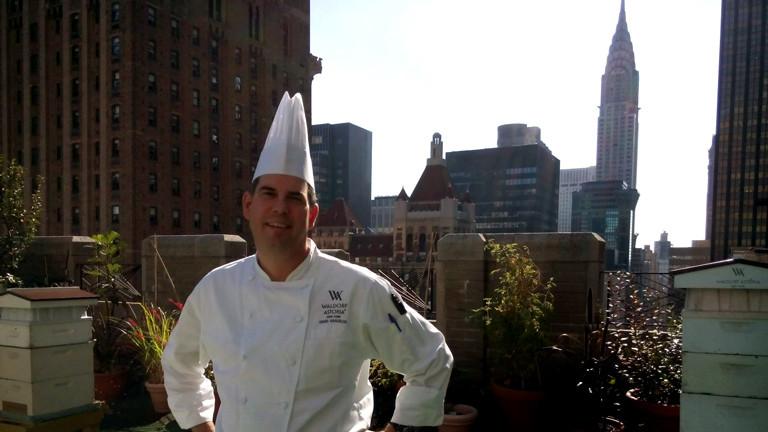 Waldorf-Chefkoch David steht auf dem Dach vor einem Bienenstock.